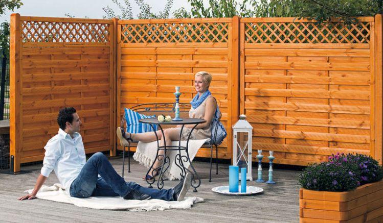 """Die Zaunserie """"Brügge"""" aus Kiefernholz mit einem kleinmaschigen Rankgitter ist in 3 verschiedenen Ausführungen erhältlich und fügt sich harmonisch in Ihren Gartenbereich ein. Die Lamellen sind im Farbton """"Pinie"""" lasiert und rostfrei Edelstahl verschraubt."""